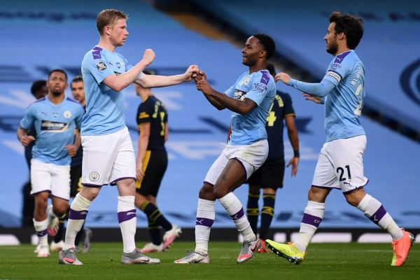 Manchester City's Belgian midfielder Kevin De Bruyne (2L) celebrates scoring his team's second goal from the penalty spot with Manchester City's English midfielder Raheem Sterling (2R) and Manchester City's Spanish midfielder David Silva during the English Premier League football match between Manchester City and Arsenal at the Etihad Stadium in Manchester, north west England, on June 17, 2020. The Premier League makes its eagerly anticipated return today after 100 days in lockdown but behind closed doors due to coronavirus restrictions. PHOTO | AFP