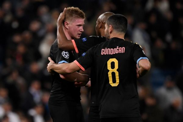 Manchester City's Belgian midfielder Kevin De Bruyne (L) and teammates celebrate their win at the end of the UEFA Champions League round of 16 first-leg football match between Real Madrid CF and Manchester City at the Santiago Bernabeu stadium in Madrid on February 26, 2020. PHOTO | AFP