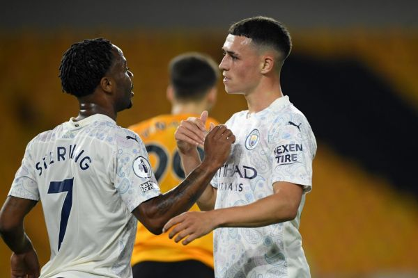Manchester City's English midfielder Raheem Sterling (L) congratulates Manchester City's English midfielder Phil Foden (R) after he celebrates scoring his team's second goal during the English Premier League football match between Wolverhampton Wanderers and Manchester City at the Molineux stadium in Wolverhampton, central England on September 21, 2020. PHOTO | AFP