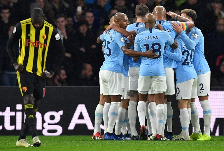 Manchester City's German midfielder Leroy Sane is mobbed by teammates after scoring the opening goal during the English Premier League football match between Watford and Manchester City at Vicarage Road Stadium in Watford, north of London on December 4, 2018. PHOTO/AFP