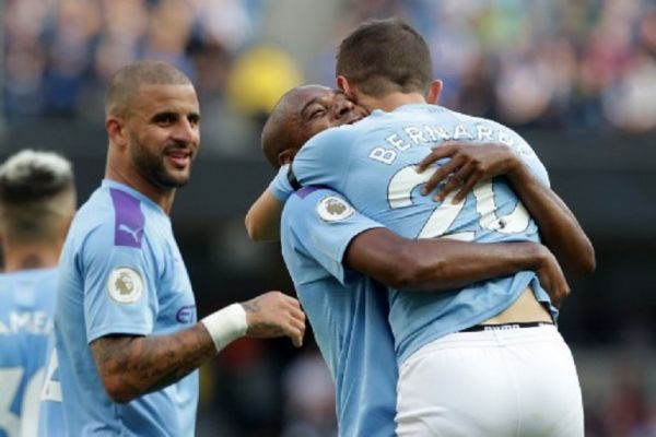 Manchester City's Portuguese midfielder Bernardo Silva (R) celebrates with Manchester City's Brazilian midfielder Fernandinho (C) after scoring their fourth goal during the English Premier League football match between Manchester City and Brighton and Hove Albion at the Etihad Stadium in Manchester, north west England, on August 31, 2019.PHOTO/ AFP