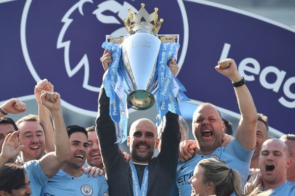 Manchester City's Spanish manager Pep Guardiola holds up the Premier League trophy as he's surrounded by his staff after their 4-1 victory in the English Premier League football match between Brighton and Hove Albion and Manchester City at the American Express Community Stadium in Brighton, southern England on May 12, 2019. PHOTO/AFP