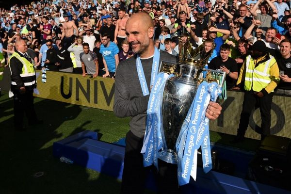 Manchester City's Spanish manager Pep Guardiola poses with the Premier League trophy after their 4-1 victory in the English Premier League football match between Brighton and Hove Albion and Manchester City at the American Express Community Stadium in Brighton, southern England on May 12, 2019. Manchester City held off a titanic challenge from Liverpool to become the first side in a decade to retain the Premier League on Sunday by coming from behind to beat Brighton 4-1 on Sunday. PHOTO/AFP