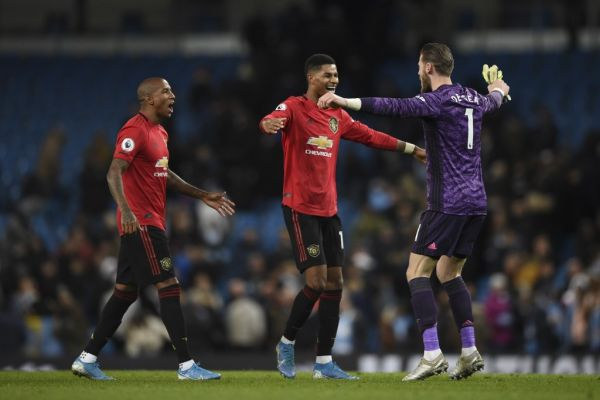 Manchester United's English defender Ashley Young, Manchester United's Spanish goalkeeper David de Gea and Manchester United's English striker Marcus Rashford celebrate victory at the end of the English Premier League football match between Manchester City and Manchester United at the Etihad Stadium in Manchester, north west England, on December 7, 2019. PHOTO \ AFP