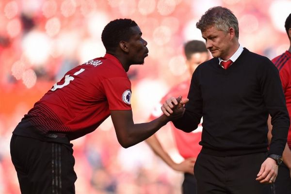 Manchester United's French midfielder Paul Pogba (L) shakes hands with Manchester United's Norwegian manager Ole Gunnar Solskjaer (R) on the pitch after the English Premier League football match between Manchester United and Cardiff City at Old Trafford in Manchester, north west England, on May 12, 2019. Cardiff won the game 2-0. PHOTO | AFP