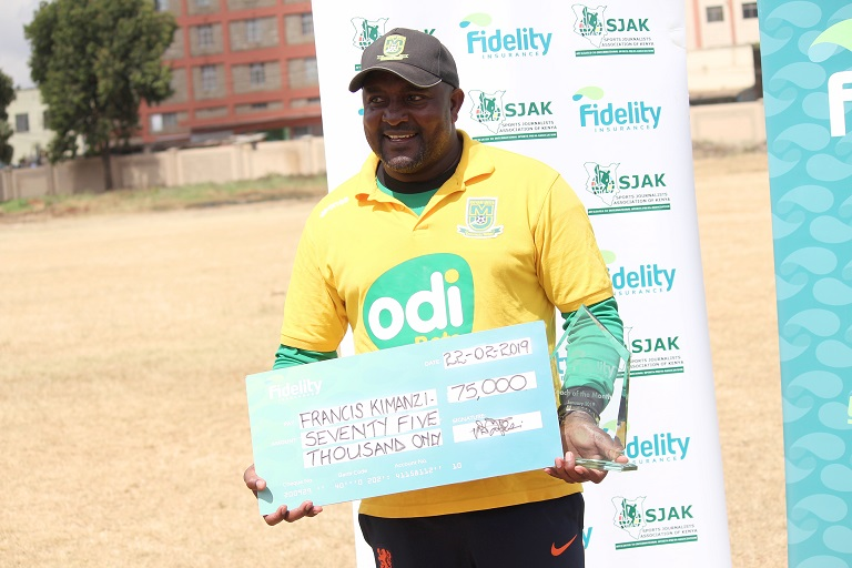 Mathare United Coach Francis Kimanzi (left) is presented with the Fidelity Insurance Coach of the Month gong by the company's Marketing Manager Nicholas Malesi at Goan institute. PHOTO/SJAK