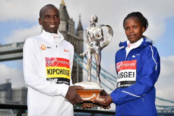Men's elite race winner Kenya's Eliud Kipchoge (L) and Women's elite race winner Kenya's Brigid Kosgei pose with the trophy during the London Marathon winners' photocall at Tower Bridge in central London on April 29, 2019. PHOTO | AFP