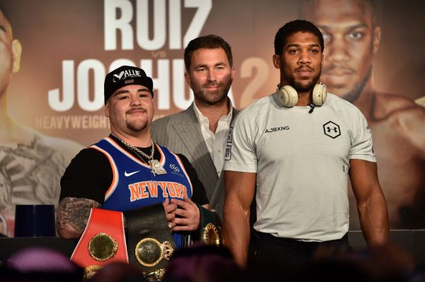 "Mexican-American heavyweight boxing champion Andy Ruiz Jr (L) Eddie Hearn (C) and British heavyweight boxing challenger Anthony Joshua (R) are pictured during their press conference in Diriyah in the Saudi capital Riyadh, on December 4, 2019, ahead of the upcoming ""Clash on the Dunes"". The hotly-anticipated rematch between Ruiz Jr and British challenger Anthony Joshua is scheduled to take place in Diriya, near the Saudi capital on December 7. PHOTO 