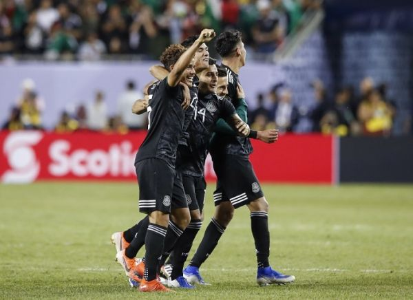 Mexico's midfielder Jonathan dos Santos (L) celebrates with teammates after defeating the United States during the second half of 2019 Concacaf Gold Cup final football match between USA and Mexico on July 7, 2019 at Soldier Field stadium in Chicago, Illinois. Mexico defeated the US 1-0. PHOTO | AFP