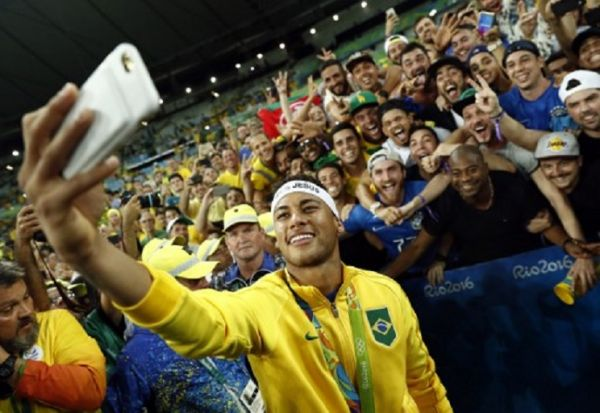 n this file photo taken on August 20, 2016, Brazil's forward Neymar poses for a selfie with fans as they celebrate after the Rio 2016 Olympic Games men's football gold medal match between Brazil and Germany at the Maracana stadium in Rio de Janeiro. PHOTO/ AFP