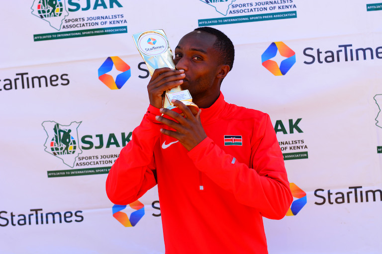 National cross country champion Amos Kirui savours the moment with his SPOM Trophy for February 2019 at Siwot, Keringet Town,Nakuru County. PHOTO/Courtesy