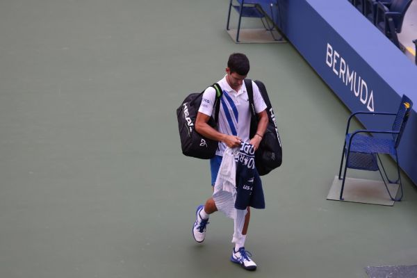 Novak Djokovic of Serbia walks off the court after being defaulted due to inadvertently striking a lineswoman with a ball hit in frustration during his Men's Singles fourth round match against Pablo Carreno Busta of Spain on Day Seven of the 2020 US Open at the USTA Billie Jean King National Tennis Center on September 6, 2020 in the Queens borough of New York City.  PHOTO | AFP