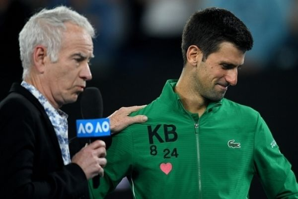 Novak Djokovic of Serbia wears the initials and numbers of Kobe Bryant on his jacket ashe is interviewed by John McEnroe after winning his fifth round match against Milos Raonic of Canada on day nine of the Australian Open tennis tournament at Rod Laver Arena in Melbourne, Tuesday, January 28, 2020. PHOTO | AFP