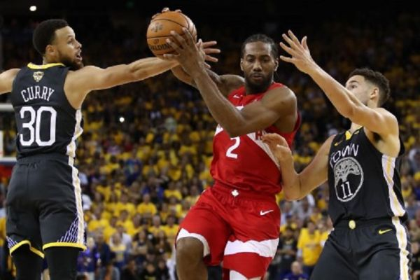OAKLAND, CALIFORNIA - JUNE 07: Kawhi Leonard #2 of the Toronto Raptors drives to the basket against Stephen Curry #30 and Klay Thompson #11 of the Golden State Warriors in the second half during Game Four of the 2019 NBA Finals at ORACLE Arena on June 07, 2019 in Oakland, California. PHOTO/ AFP