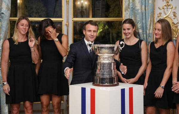Pauline Parmentier, Caroline Garcia, Alize Cornet and Fiona Ferro of the French women tennis team abd French President Emmanuel Macron (C) pose during a reception at the Elysee presidential palace in Paris on November 12, 2019, two days after they won the Fed Cup competition. PHOTO | AFP