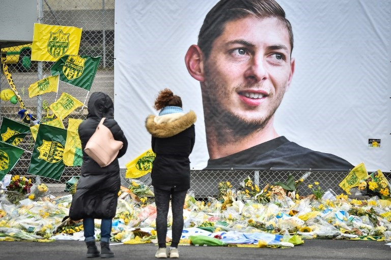 People look at yellow flowers displayed in front of the portrait of Argentinian forward Emiliano Sala at the Beaujoire stadium in Nantes, on February 8, 2019. PHOTO/AFP