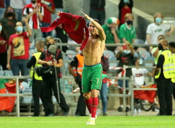 Portugal's Cristiano Ronaldo holds up his shirt to to the fans after scoring his sides second goal during the 2022 FIFA World Cup Qualifying match at the Estadio Algarve, Portugal.