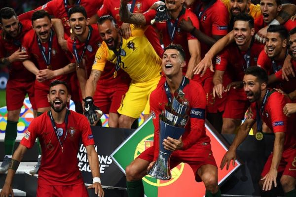 Portugal's forward Cristiano Ronaldo (C) holds the trophy as he celebrates with teammates after the UEFA Nations League final football match between Portugal and The Netherlands at the Dragao Stadium in Porto on June 9, 2019. PHOTO/AFP