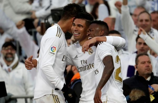 Real Madrid's Brazilian midfielder Carlos Casemiro (C) celebrates with his teammates Raphael Varane (L) and Vinicius Junior (R) after scoring his first and team's second goal with a header during the Spanish league (La Liga) football match between Real Madrid CF and Sevilla FC at the Santiago Bernabeu Stadium in Madrid, Spain on January 18, 2020. PHOTO | AFP