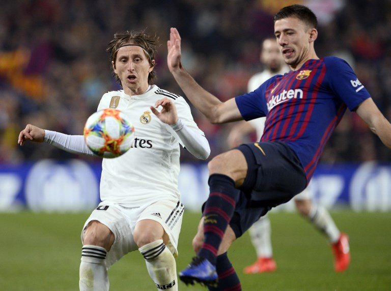 Real Madrid's Croatian midfielder Luka Modric (L) vies with Barcelona's French defender Clement Lenglet during the Spanish Copa del Rey (King's Cup) semi-final first leg football match between FC Barcelona and Real Madrid CF at the Camp Nou stadium in Barcelona on February 6, 2019. PHOTO/AFP
