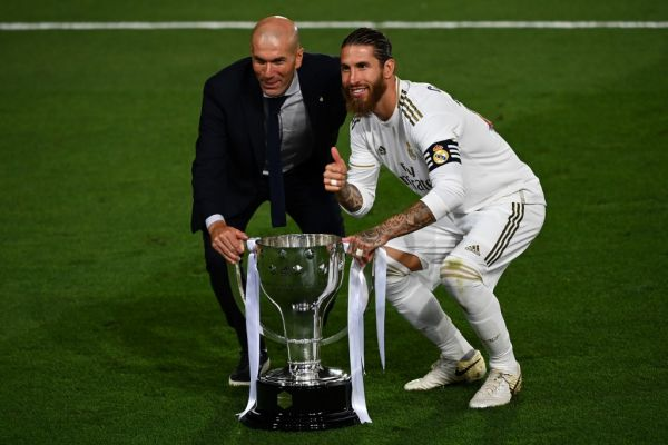 Real Madrid's French coach Zinedine Zidane (K) and Real Madrid's Spanish defender Sergio Ramos celebrate with the trophy after winning the Ligs title after the Spanish League football match between Real Madrid CF and Villarreal CF at the Alfredo di Stefano stadium in Valdebebas, on the outskirts of Madrid, on July 16, 2020. PHOTO | AFP