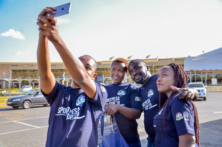 SNAPPING HAPPINESS: Winners of the 'Win A Trip' online competition take a selfie at the Jomo Kenyatta International Airport, Nairobi ahead of their flight to Dar-es-Salaam, Tanzania for the 2019 SportPesa Cup final on Saturday, January 26, 2019. PHOTO/SPN