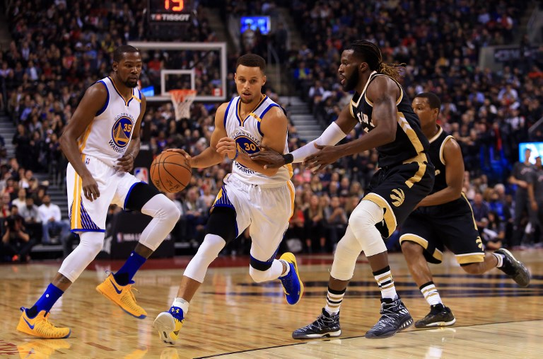 Steph Curry #30 of the Golden State Warriors dribbles the ball as DeMarre Carroll #10 of the Toronto Raptors defends during the first half of an NBA game at Air Canada Centre on November 16, 2016 in Toronto, Canada. PHOTO/AFP