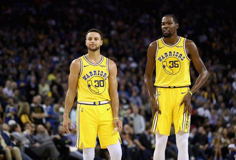Stephen Curry #30 and Kevin Durant #35 of the Golden State Warriors stand on the court during their game against the Washington Wizards at ORACLE Arena on October 24, 2018 in Oakland, California. PHOTO/AFP
