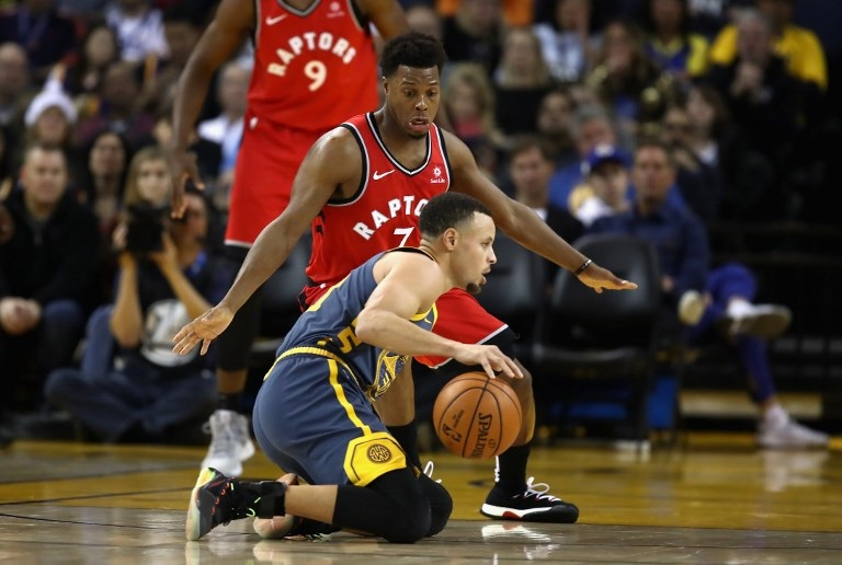 Stephen Curry of the Golden State Warriors dribbles on his knees while being guarded by Kyle Lowry of the Toronto Raptors at ORACLE Arena on December 12, 2018 in Oakland, California. PHOTO/AFP