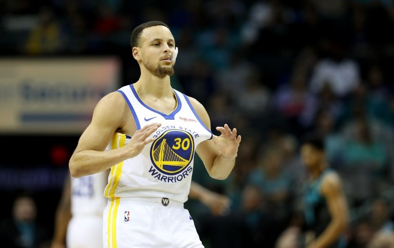 Stephen Curry of the Golden State Warriors grabs his jersey against the Charlotte Hornets during their game at Spectrum Center on February 25, 2019 in Charlotte, North Carolina. PHOTO/AFP