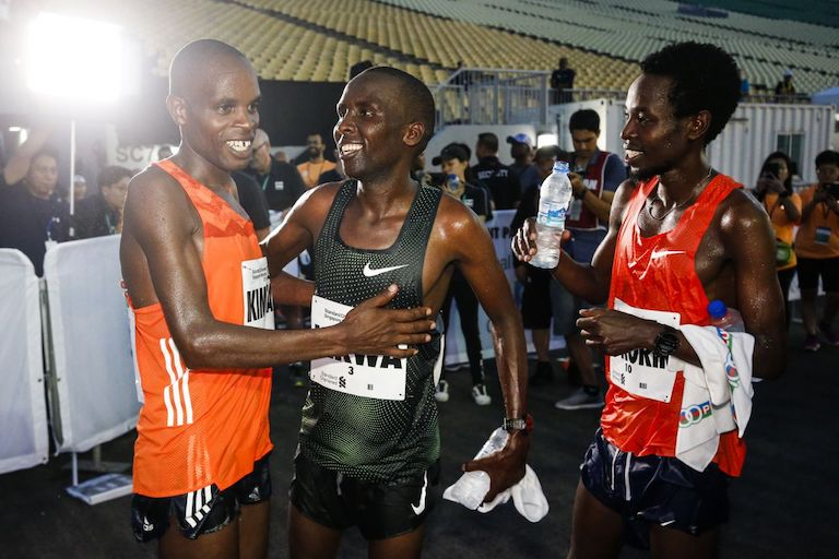 The Kenya men's winners (from left: third-placed Andrew Kimtai, runner-up Felix Kirwa and champion Joshua Kipkorir) celebrate their feat at the Standard Chartered Singapore Marathon. PHOTO/AFP