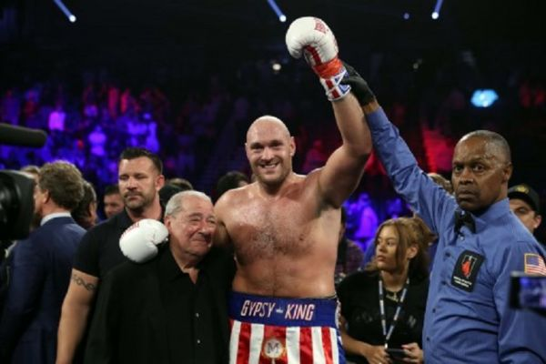 Tyson Fury (C) poses with boxing promoter Bob Arum (L) and referee Kenny Bayless after defeating Tom Schwarz during a heavyweight fight at MGM Grand Garden Arena on June 15, 2019 in Las Vegas, Nevada. PHOTO/ AFP