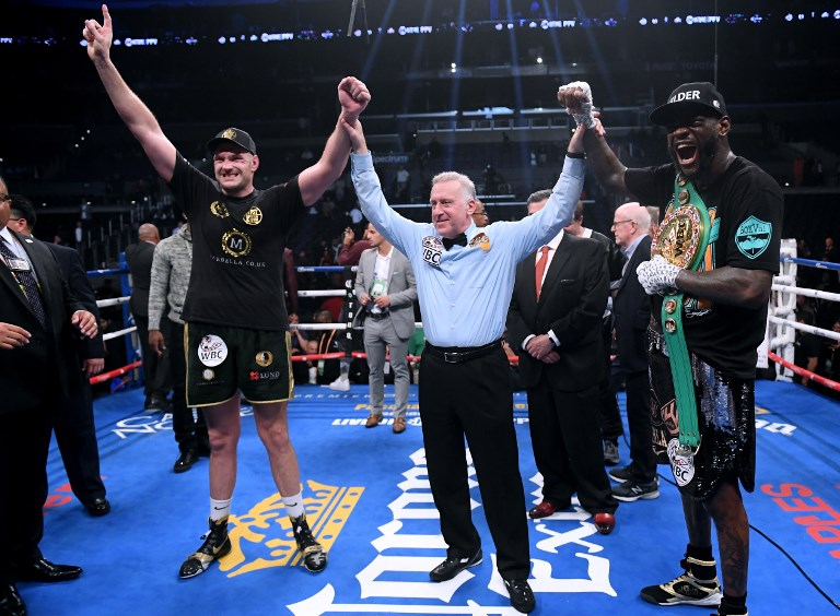 Tyson Fury and Deontay Wilder pose for a photo with referee Jack Reiss after fighting to a draw during the WBC Heavyweight Championship at Staples Center on December 1, 2018 in Los Angeles, California. PHOTO/AFP