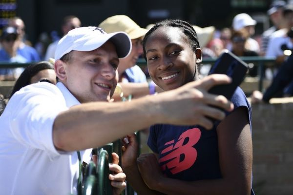 US player Cori Gauff (R) poses for a selfie with fans after a session on the practice courts at The All England Tennis Club in Wimbledon, southwest London, on July 4, 2019, on the fourth day of the 2019 Wimbledon Championships tennis tournament. PHOTO/AFP