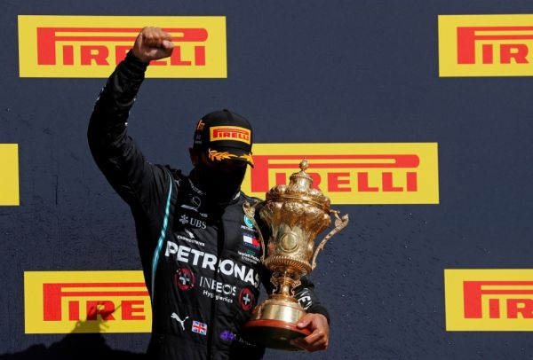 Winner Mercedes' British driver Lewis Hamilton celebrates with his trophy on the podium after the Formula One British Grand Prix at the Silverstone motor racing circuit in Silverstone, central England on August 2, 2020. Lewis Hamilton survived a dramatic finale to win the British Grand Prix on Sunday, just making it across the line on three tyres to beat a fast closing Max Verstappen on Red Bull. The defending world champion claimed his seventh British Grand Prix win as Ferarri's Charles Leclerc came third and Daniel Ricciardo of Renault fourth. PHOTO | AFP